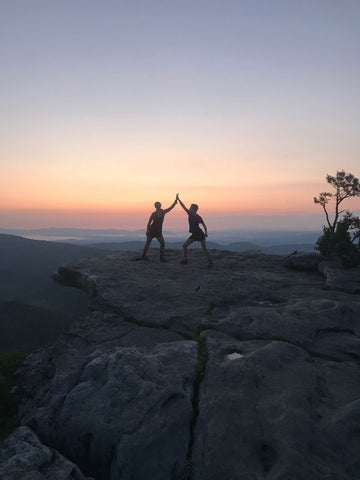 two hikers on a mountain top at sunset high fiving each other silhoutted against the purple, peach, and yellow sky