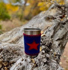 stainless steel tumbler wrapped in navy blue wool sleeve with orange star on it sitting on a stump with fall colored forest in background