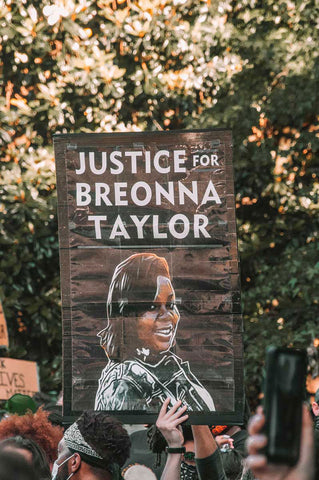 white hand holding a sign saying justice for Breonna Taylor