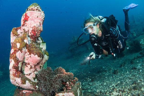 woman diver looking at underwater statue of a woman with a bed of sea anemones growing in her lap