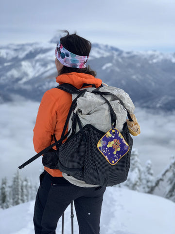woman backpacking in winter wearing an orange coat standing atop a snow covered mountain vista overlooking soft curvaceous mountain peaks with a beehive Kula Cloth attached to her backpack