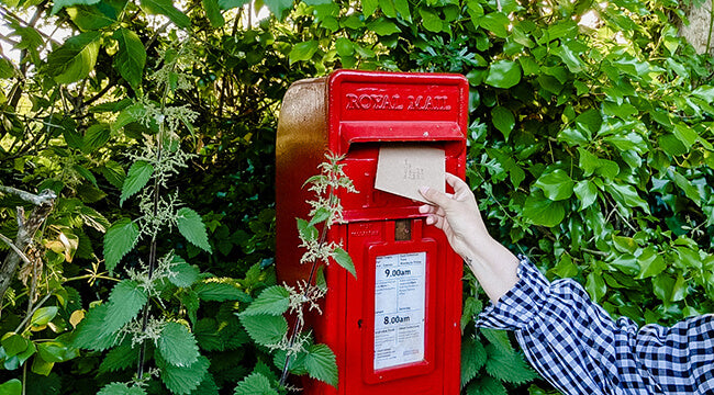 Birthday card being posted in red letterbox UK
