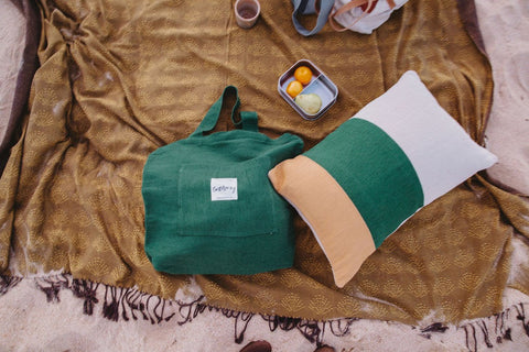plastic free bag, blanket and cushion by Earth Worthy. Ethically handmade. tonal colours of green, mustard and natural displayed on the beach