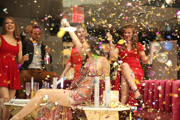Group of friends partying with a multicolor confetti falling