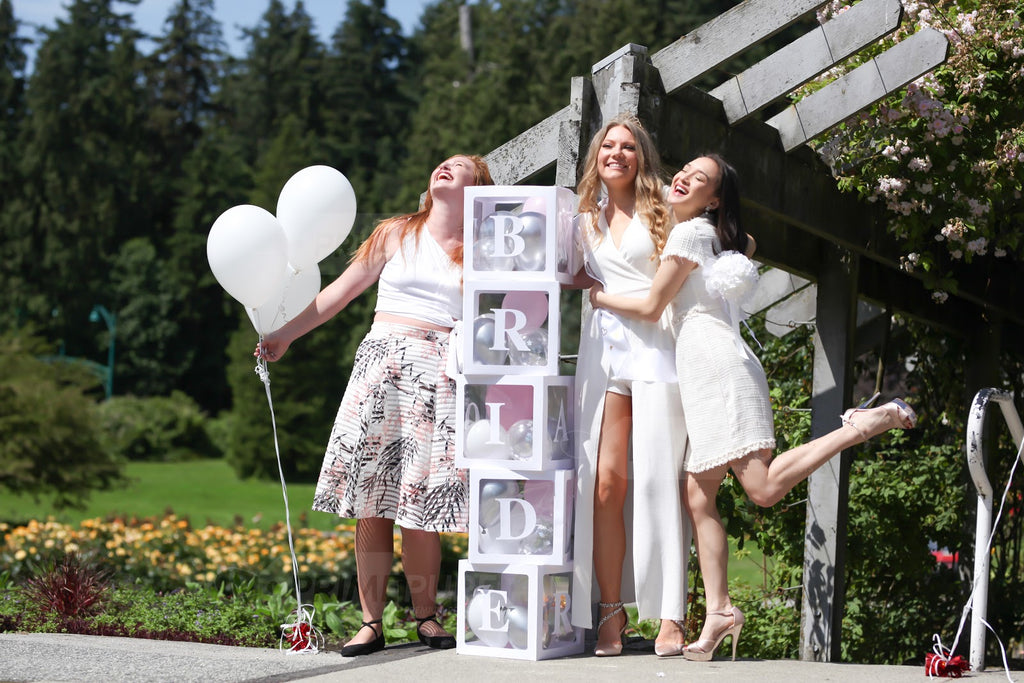 """3 girls with a custom letter """"BRIDE"""" boxes decorations"""