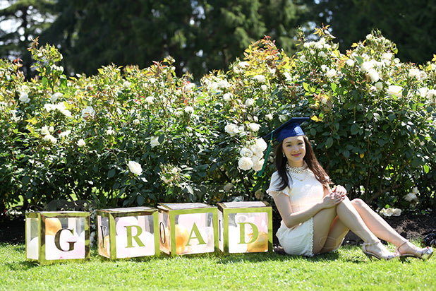 A girl with custom letter 'GRAD' boxes