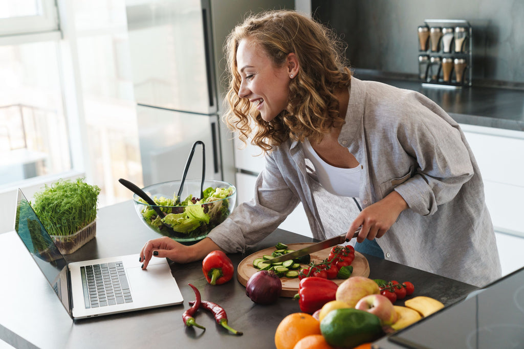 Woman doing multi-task (Chopping the vegetables while browsing online)
