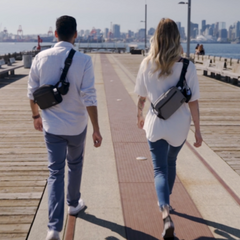 Man and woman showcasing Easier Journey's crossbody bag and fanny pack combo on a walk. On-the-go gear. Hoodies, scarves, germkeys and collapsible water bottles..