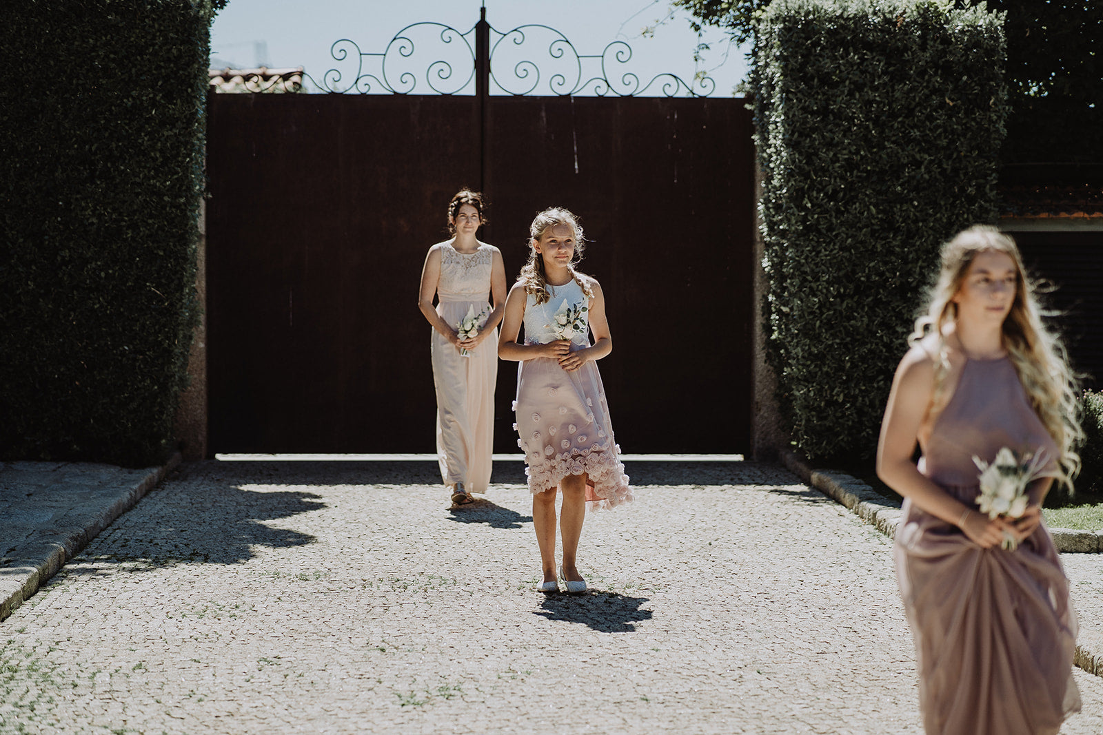 The Bridesmaids walking down the isle, in the garden setting, holding flowers.