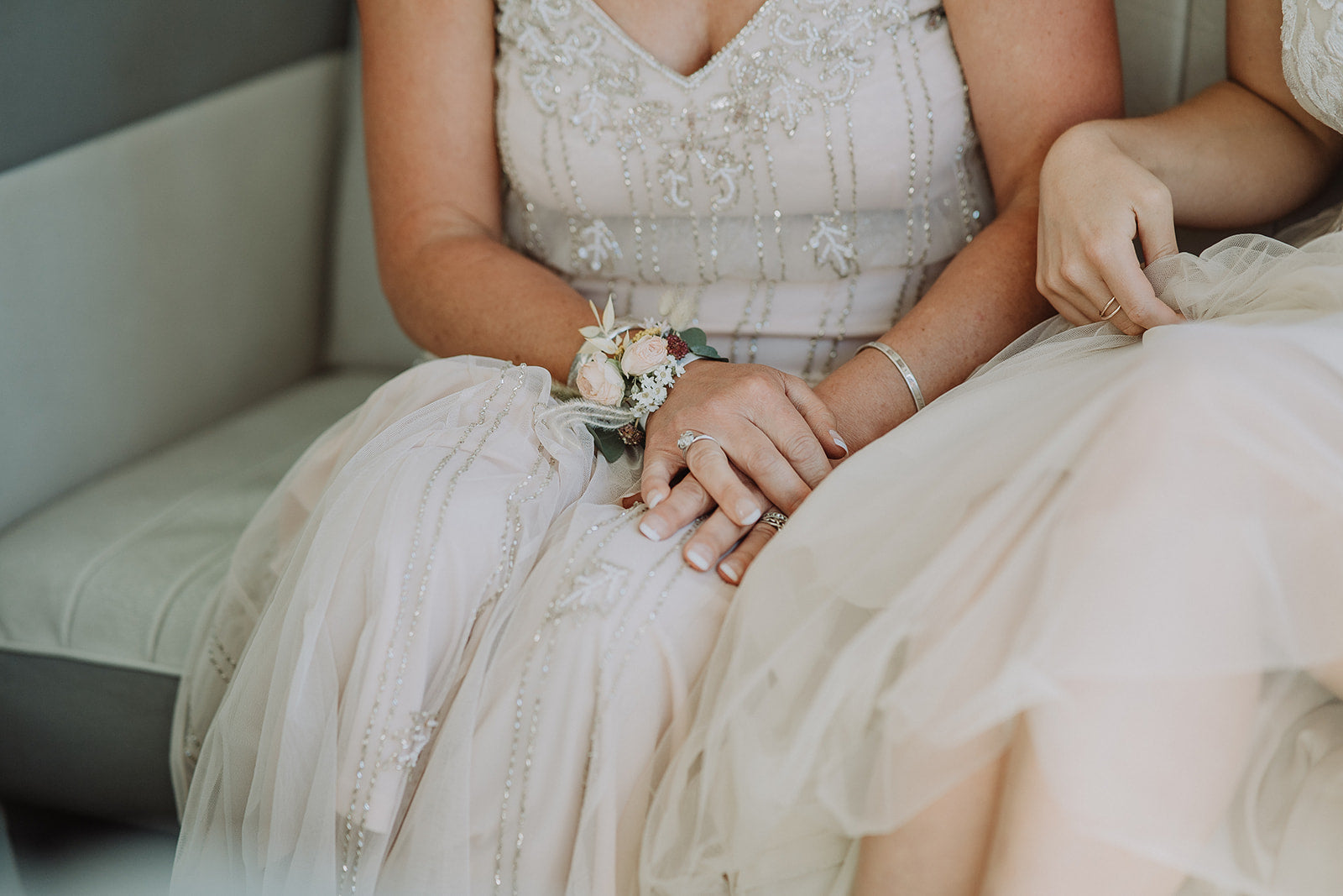 Eco-friendly wedding corsage, worn on the wrist. Close up of two women, seated, wearing bridal and mother of the bride dresses in neutral colours.