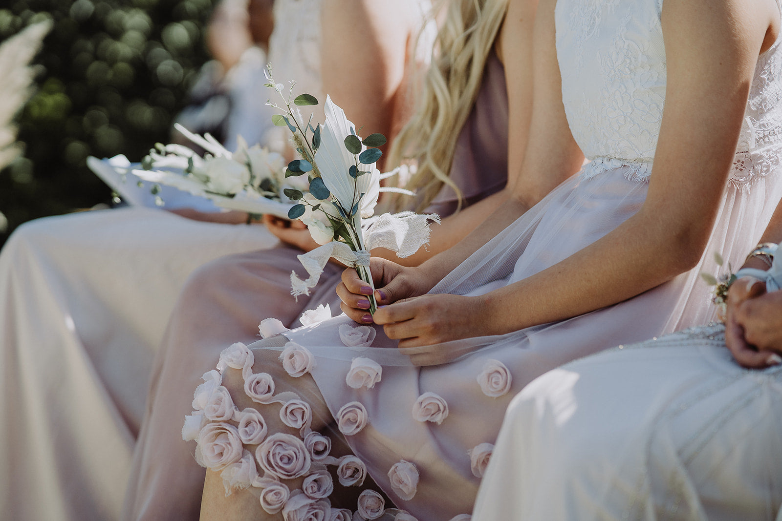 The Bridesmaid holds her flowers in hand. Her dress is embellished with fabric roses.