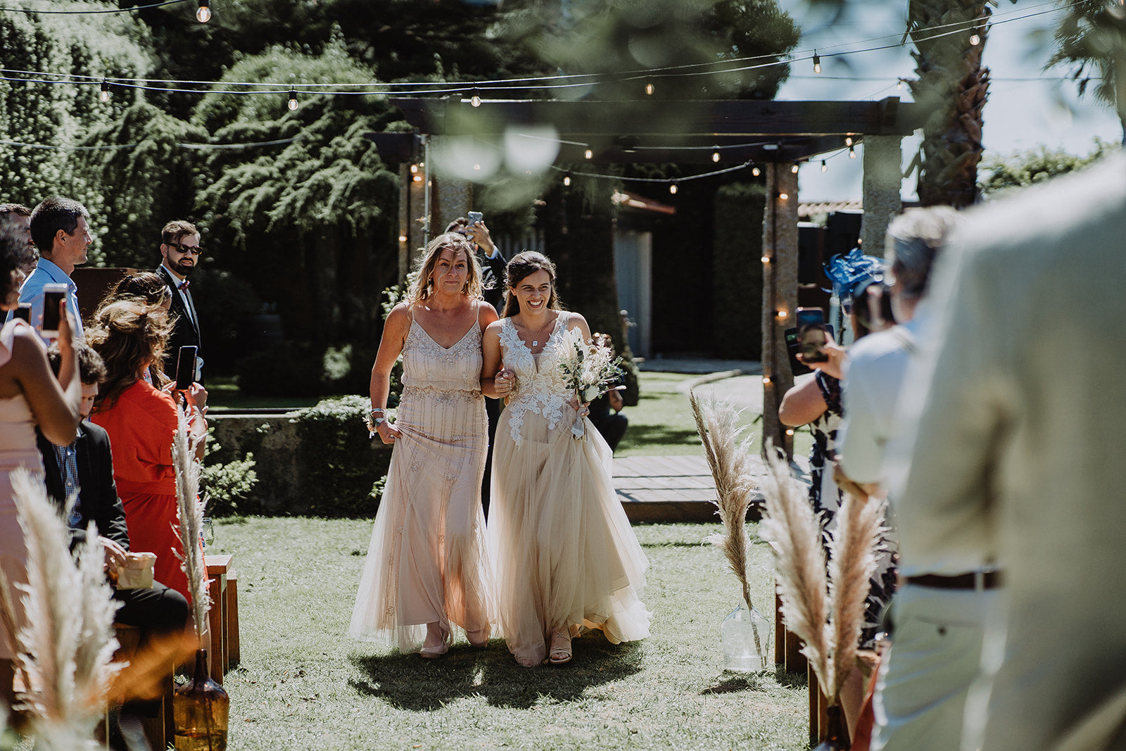 Bride Jade, walking down the isle with her Mum, wearing their second hand wedding outfits.