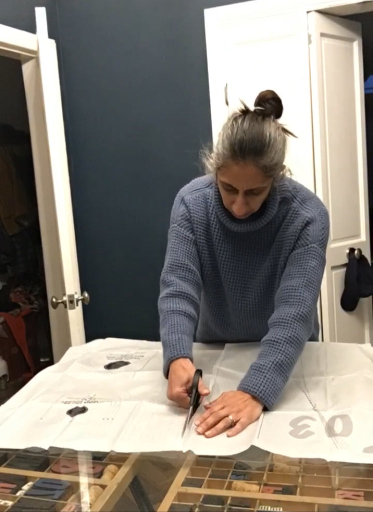 Saywood Social Club - Make With Mandi creating her home sewing patterns. Mandi is wearing and blue sweater and cutting out the paper patterns on a table at home.