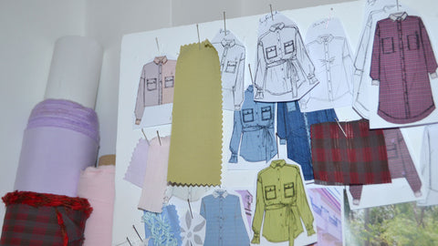 Saywood sketches pinned to a board with fabrics for the design process. The top of fabric rolls can be seen to the left of the image.
