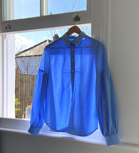 Saywood Edi Volume Sleeve Shirt Pale Blue hanging in open window to air, with sunlight shining in.