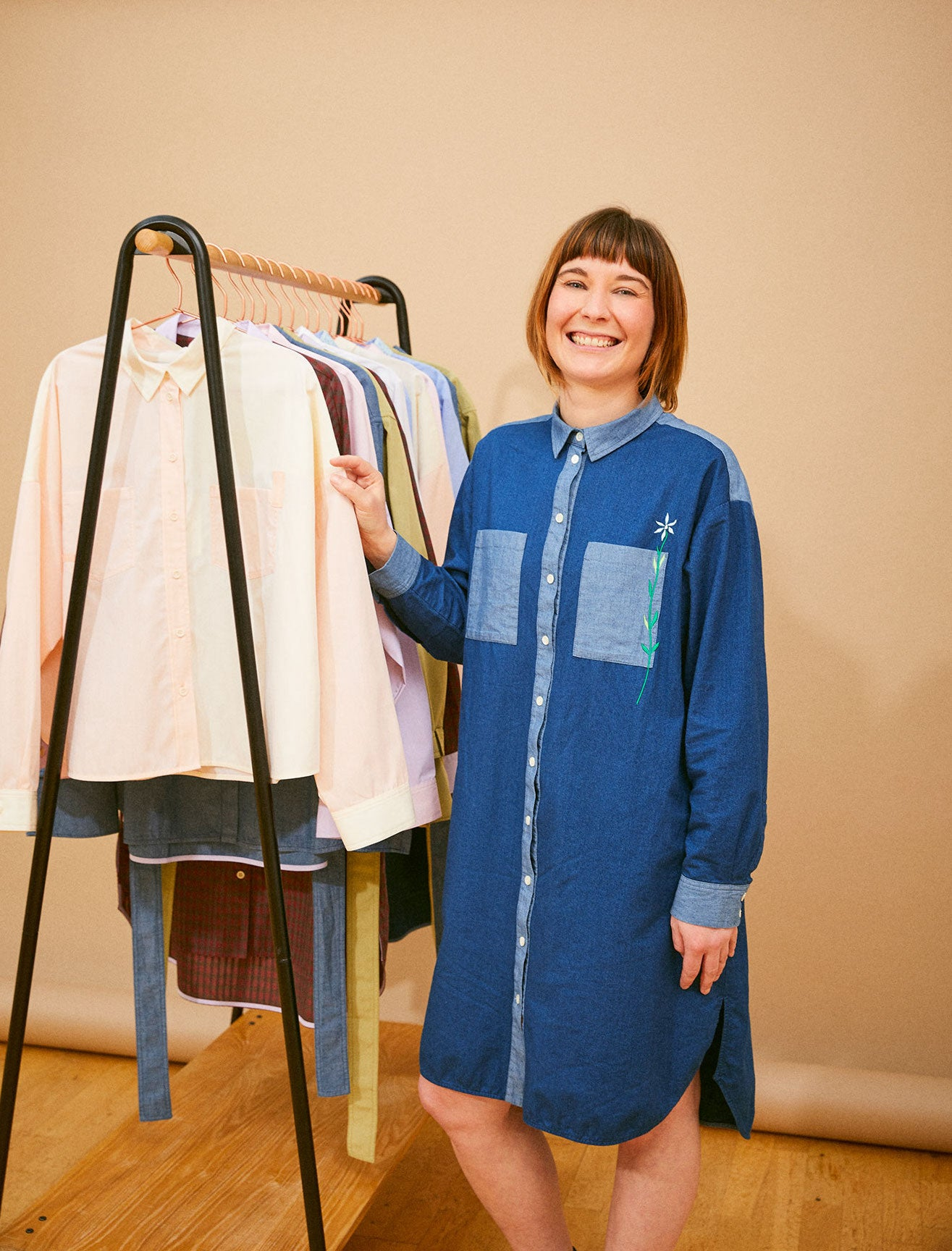 Slow fashion and ethical brand Saywood's founder Harriet, standing next to a rail of women's clothing - shirts from the first collection.