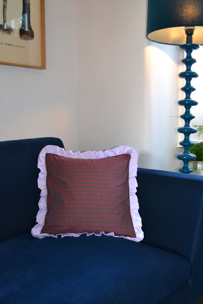 Home Textiles Saywood Ruffle Cushion from deadstock, in red check with a lilac frill edge. The cushion is placed on a navy velvet sofa, with a blue tall lamp and picture from visible