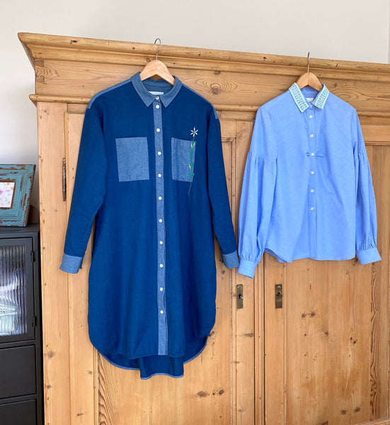 Saywood Etta Shirtdress in denim and Edi Volume Sleeve Shirt in pale blue recycled cotton hanging on a wooden wardrobe to finish drying on a hanger.
