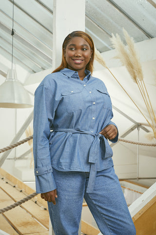 Japanese denim womens shirts, Saywood Zadie Boyfriend Shirt in light wash denim, belt tied. Model stands relaxed, with one hand on waist. Pampus grass in background of a skylight room