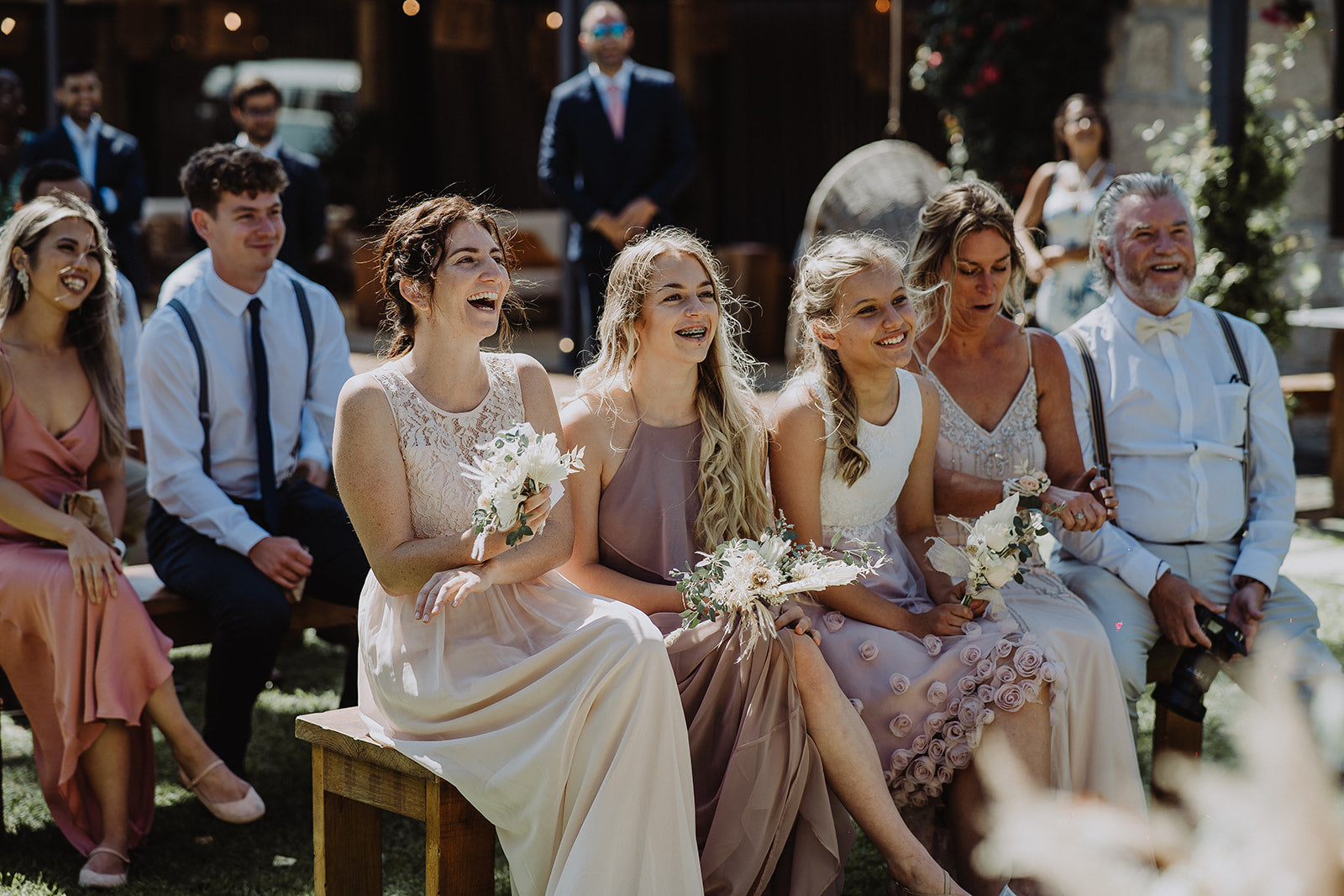 The Bridesmaids and Mother of the Bride seated at the outdoor ceremony, wearing their pre-loved dresses, laughing.