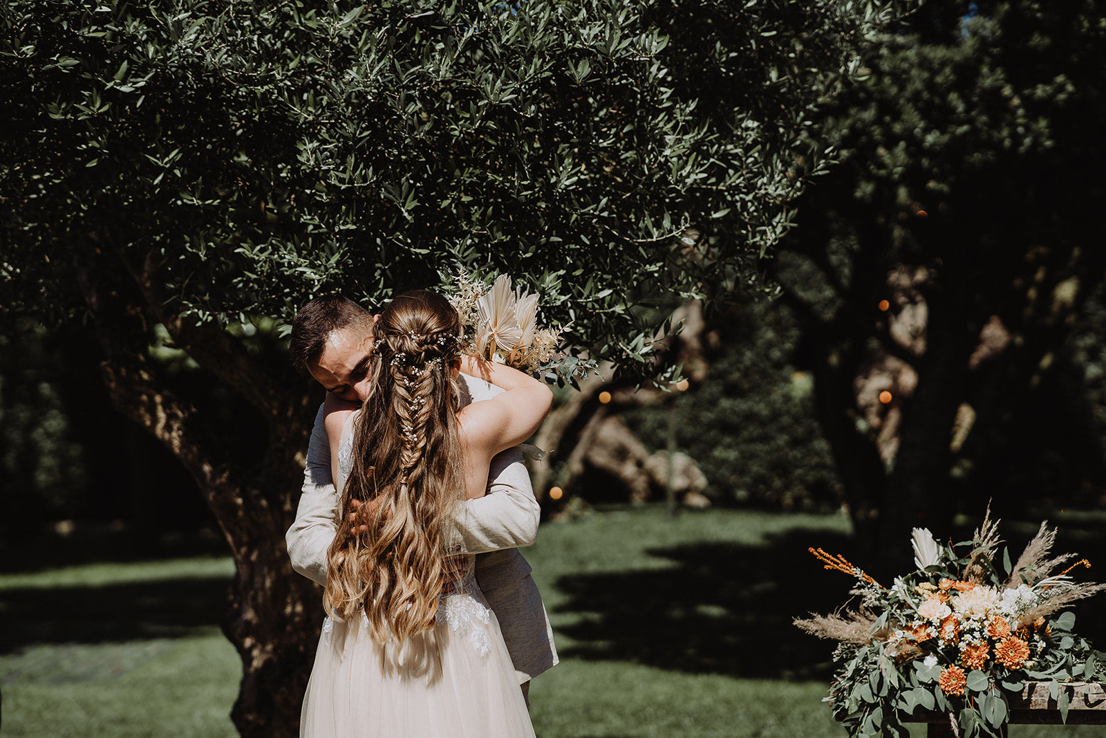 Under the trees the Bride and Groom embrace. The Bride's plaited hair is seen trailing beautifully, whilst she holds her flowers with arms wrapped around her Husband.