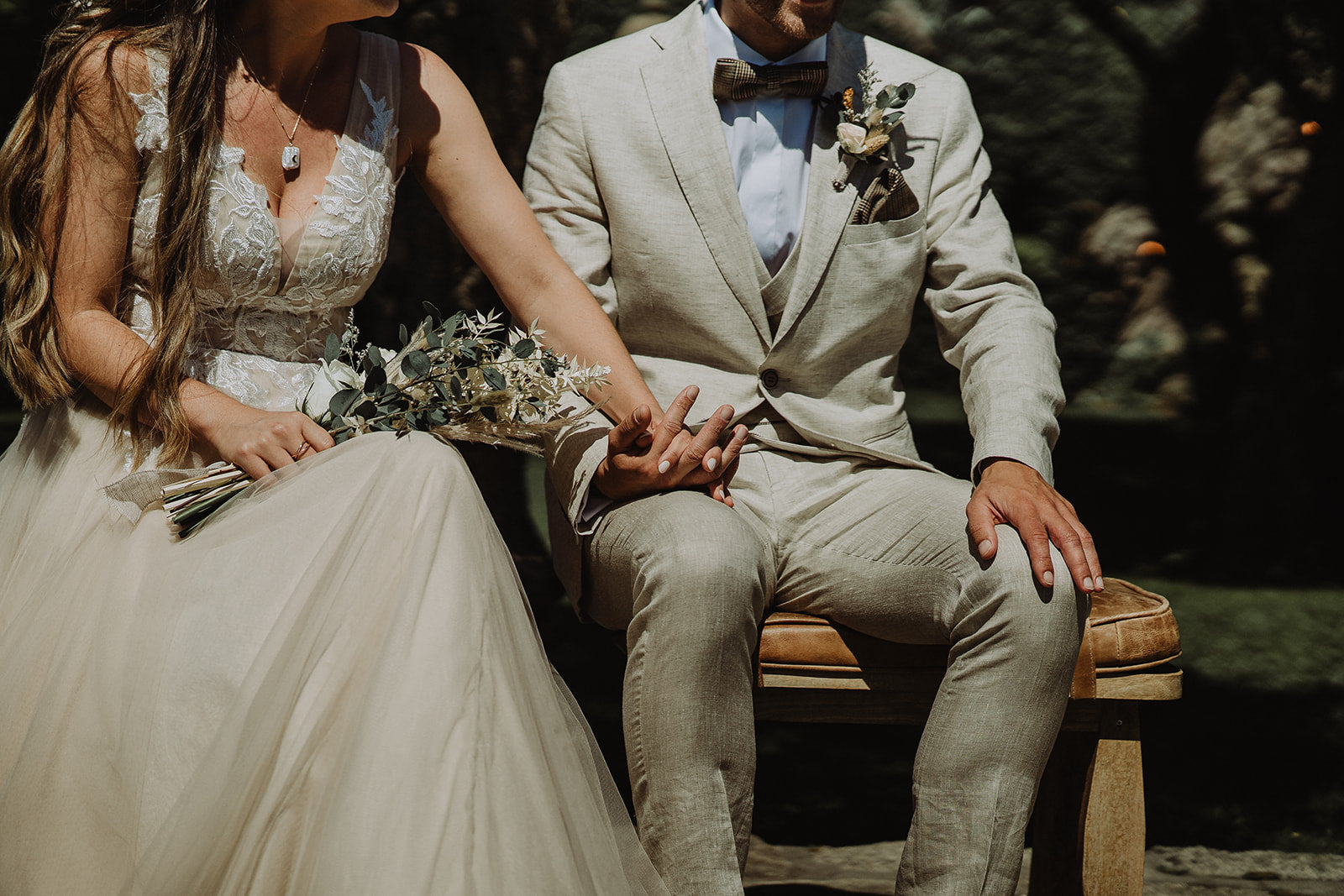 Bride and Groom wearing their pre-loved sustainable wedding dress and suit, with the Bride holding her flowers. They both hold hands.