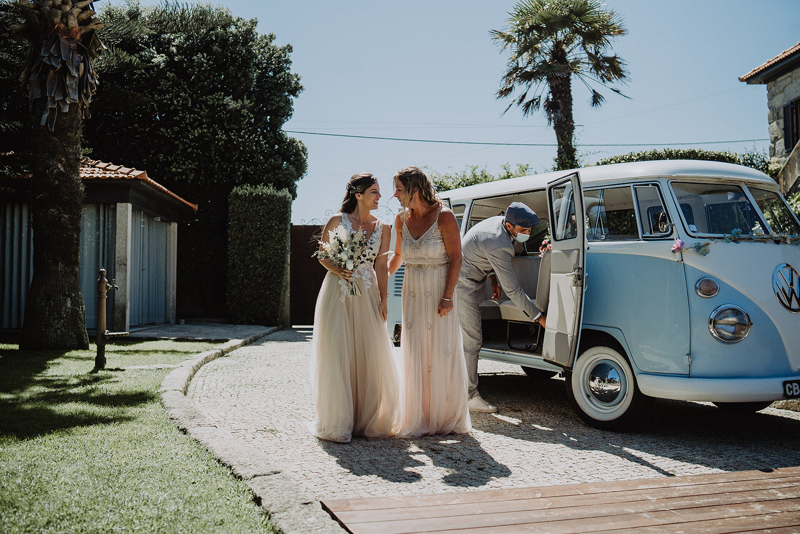 The Bride and Mother of the Bride stand together in their beautiful pre-loved dresses, with the Bride holding flowers. They stand next to a light blue VW Camper Van with a palm tree in the background.