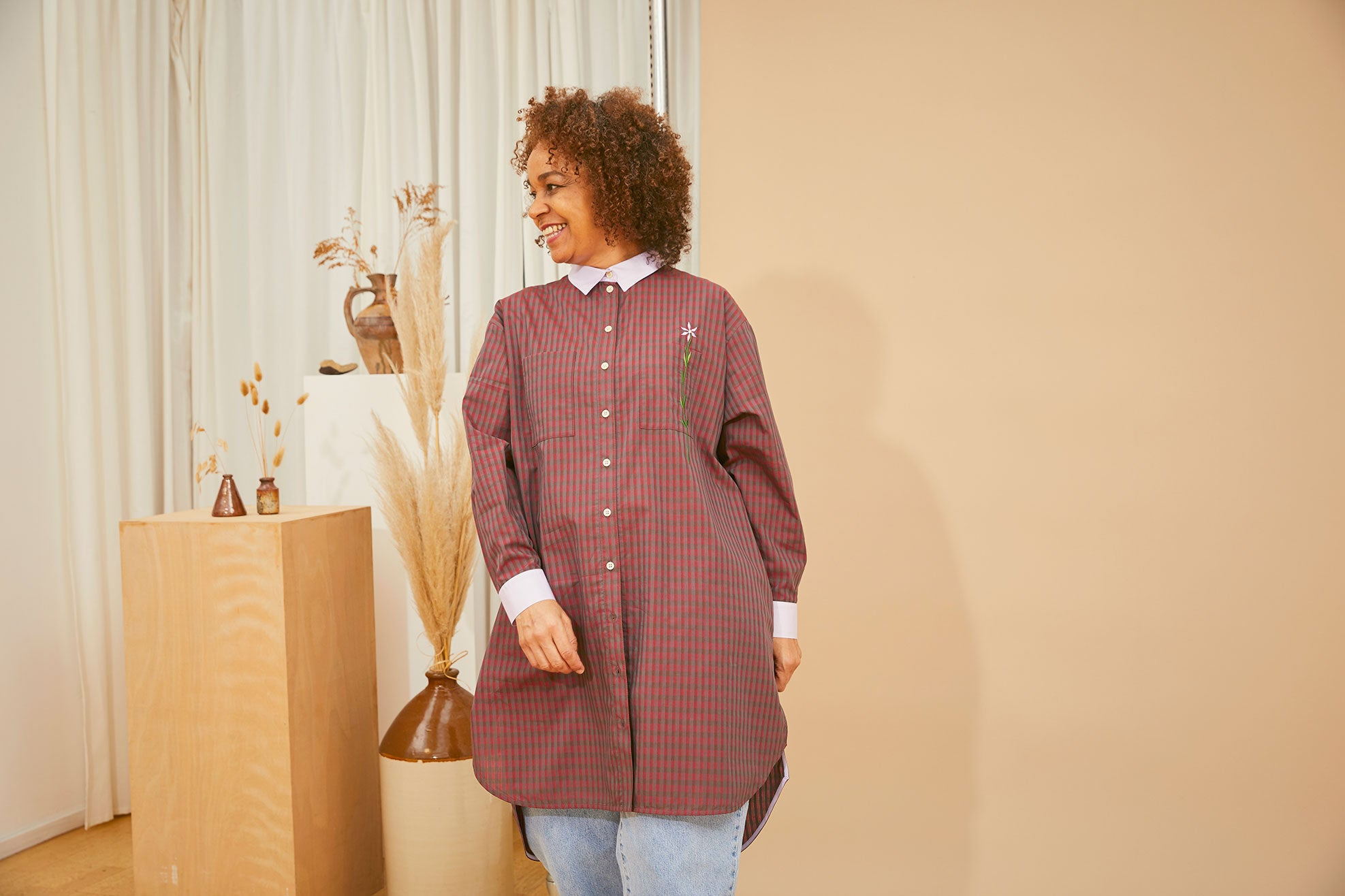 Saywood deadstock Etta Oversized Shirtdress in red check cotton, worn over jeans by model who is looking to one side and smiling, with vintage vases in the background