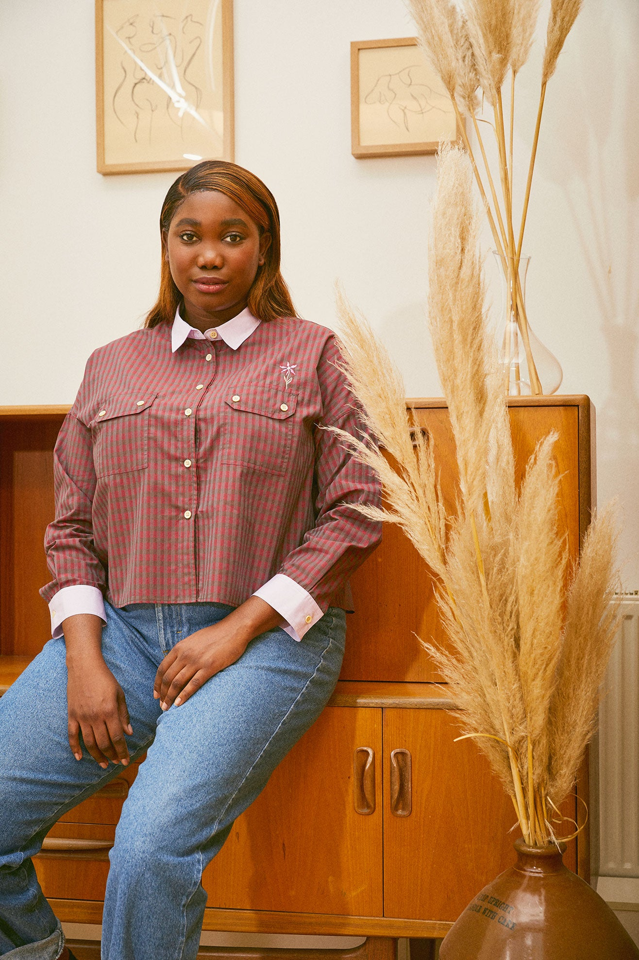 Saywood deadstock cotton Jules Utility Shirt in red check worn with jeans by model leaning against a mid century cupboard unit, with pampas grass  in a vintage vase to the right