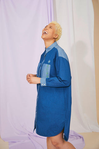Japanese Denim Saywood Etta Shirtdress worn by model who is laughing up to the ceiling and shown standing side on, with hands clasped in front of her