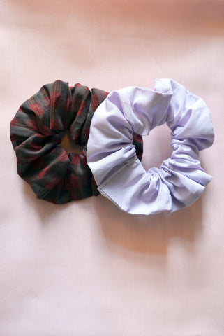 Saywood Scrunchies hair accessories made from deadstock cotton, one in red check and one in lilac.