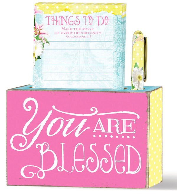 "This blox giftset from our Sunshine Daisies collection features a wood blox, notepad and pen. Brightly colored tabletop decor to lift your spirit. Inspirational message of ""you are blessed."""