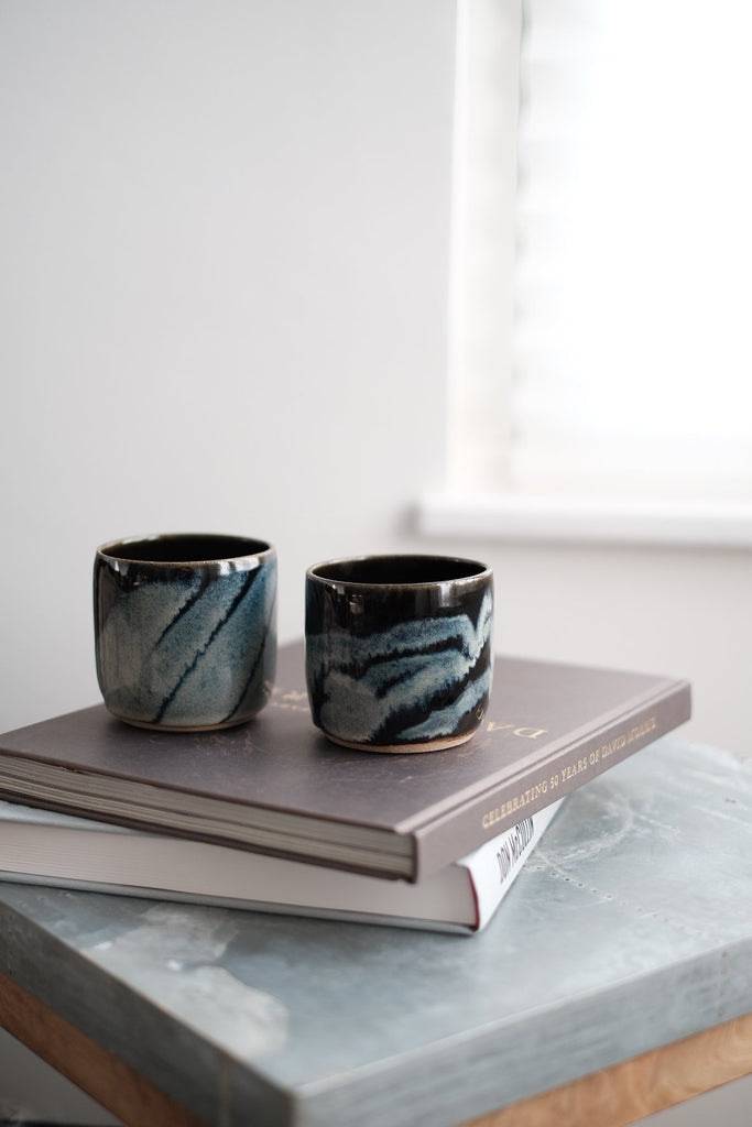 handleless ceramic mugs in a dark green glaze with white wave decoration