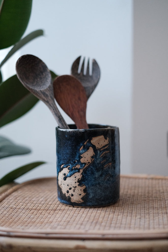 a ceramic kitchen utensil holder with blue glazing and bare clay brush stroke