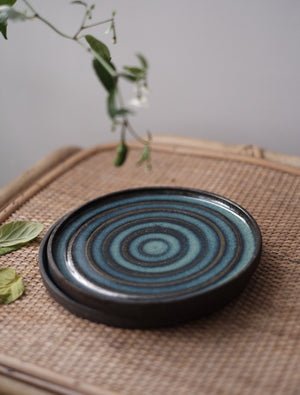 two black ceramic side plates with ring pattern glazed with blue green on top
