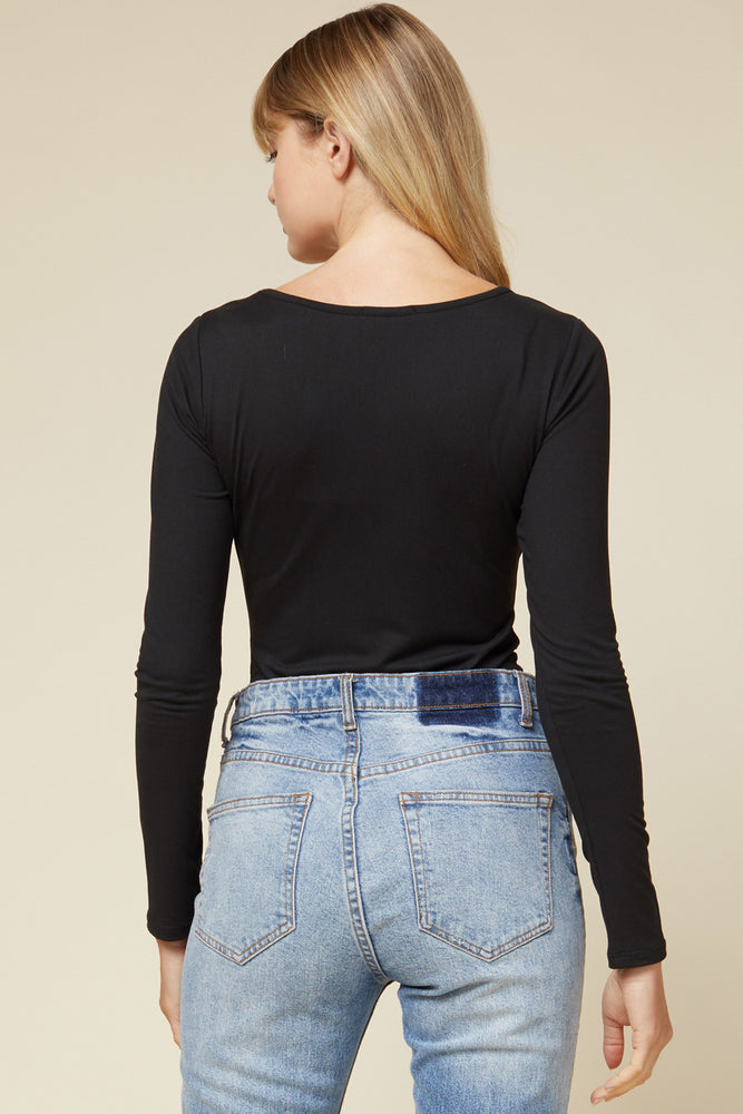 Side View of Black Scoop Neck Long Sleeve Bodysuit Paired with Blue Jeans