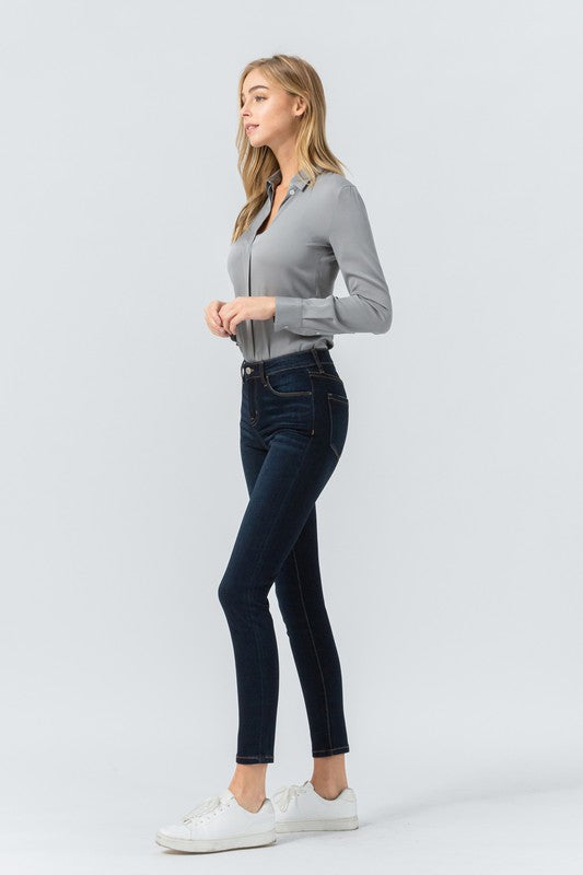 Side View of Dark Blue Mid-rise Ankle Length Skinny Jean With Pockets Paired with Gray Long Sleeve Button Down and White Sneakers