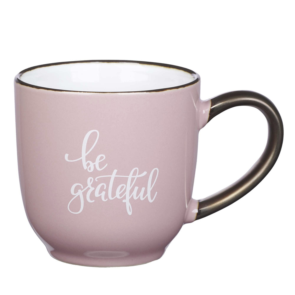 "Front View of Light Pink ""be grateful"" Mug with Bronze Handle and Rim in Front of Pink Backdrop"