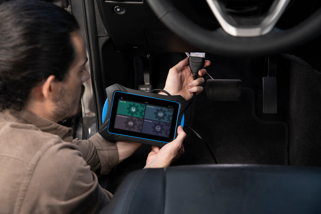 Smart Diagnostic System - OBD2 Tablet 7111 being plugged into a vehicle to complete an automotive diagnostic scan