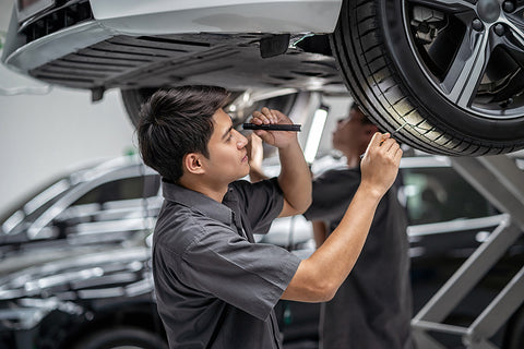 Innova Electronics_tech inspecting tires before driving