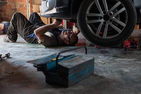 Innova electronics home mechanic inspecting the underside of a car for vehicle diagnostics