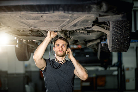 innova electronics mechanic listening to car for noises while performing vehicle diagnostics