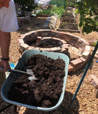 Putting compost in a Herb Spiral
