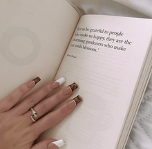 "Load image into Gallery viewer, Photograph of hand with nail art wearing a snake ring called ""slither ring"" with a book open showing a quote ""Let us be grateful to people who make us happy, they are the charming gardeners who make our souls blossom"""