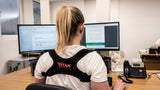 a women sat at a desk wearing a back posture corrector