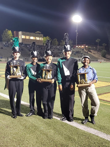 members of a high school band holding trophies on a football filed