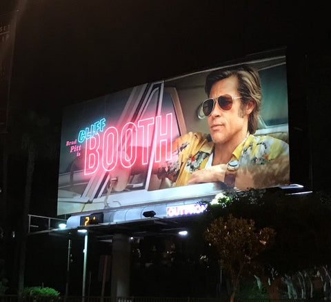 Cliff Booth wearing his Red Monkey watchband on the Sunset Strip billboard