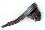 Copper colored rivets on leather guitar strap with adjustable buckle