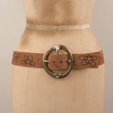 Hand-branded floral pattern with turquoise studs and large brass buckle leather belt