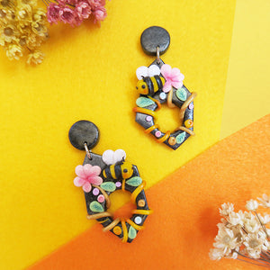 Yellow bees with pink flowers on black background earrings